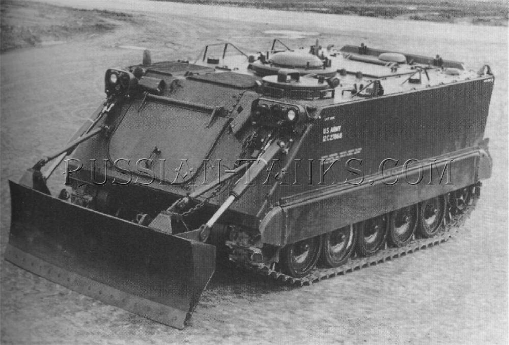 The armored personnel carrier is equipped with a 104 inch wide aluminum alloy dozer blade raised into the travel